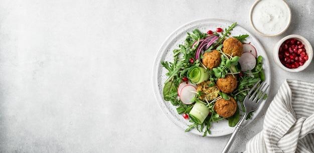 Falafel- und gemüsesalat auf einer weißen keramikplatte auf betonhintergrund kopieren raum vegetarisches lebensmittelkonzept