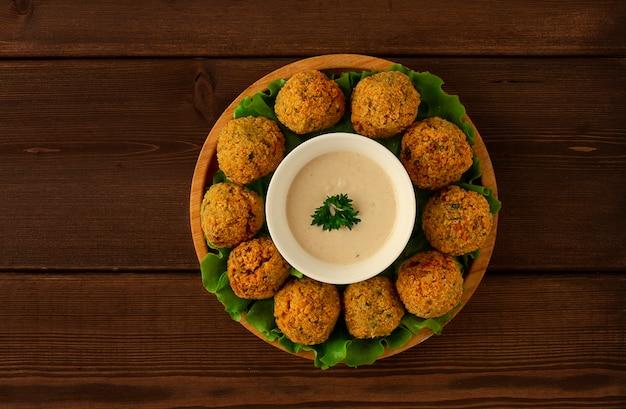 Falafelbällchen mit tahini-sauce auf einem holzbrett vegetarisches essen hausgemacht