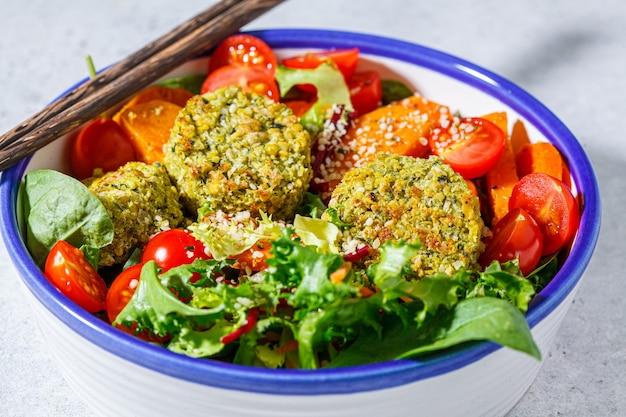 Falafelsalat mit gebackenem gemüse und tomaten in einer weißen schüssel. israelisches street food-konzept.