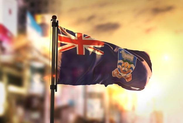 Falklandinseln flagge gegen stadt verschwommen hintergrund bei sonnenaufgang hintergrundbeleuchtung