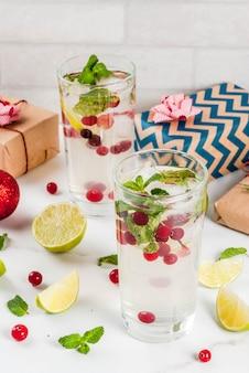 Fall- und wintererfrischungsgetränkmoosbeeremojito cocktail mit kalk und minze mit weihnachtsgeschenken und -dekorationen auf weißer tabelle