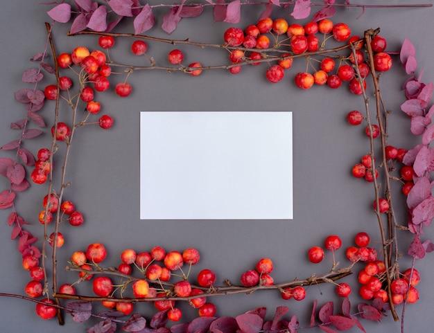 Fallen sie flatlay mit roten äpfeln und herbstlaub auf grau