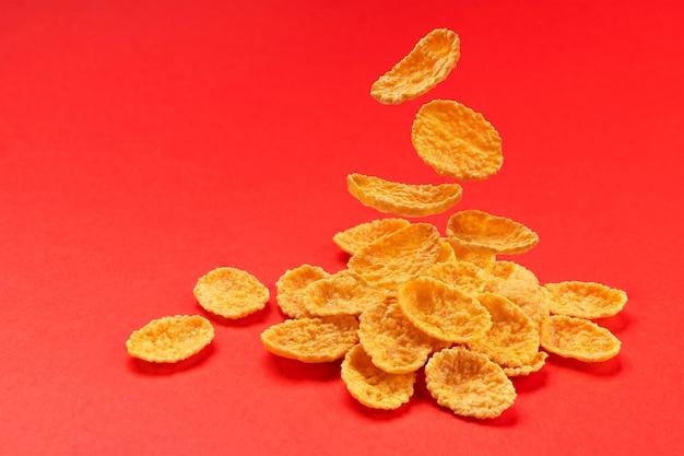 Fallende cornflakes lokalisiert auf rotem farbhintergrund, stapel des traditionellen frühstücksflocken, volle schärfentiefe