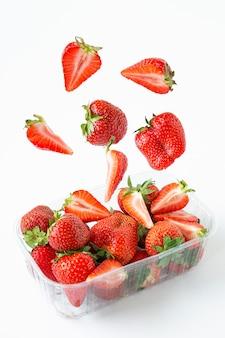 Fallende erdbeeren in einer transparenten plastikverpackung. sommersaison mit beeren.