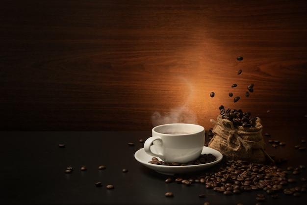 Fallende kaffeebohnen auf leinensack und kaffeetasse auf dunklem hintergrund