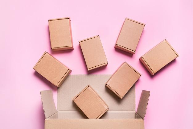Fallende pappkartons auf rosa tisch