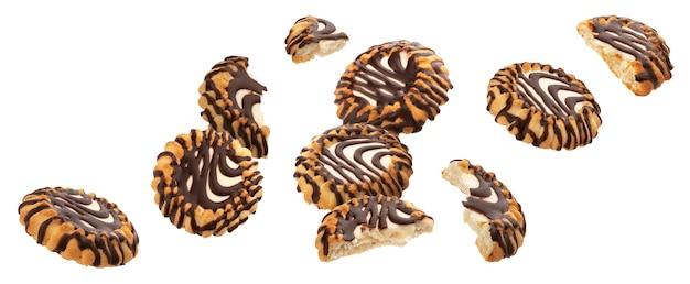 Fallende schokoladenüberzogene kekse mit milchfüllung lokalisiert auf weißem hintergrund mit beschneidungspfad