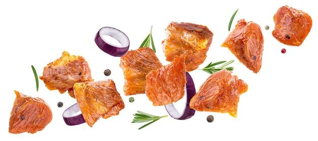 Fallende stücke von rohem schweinefleisch lokalisiert auf weißem hintergrund, mit schnittpfad, würfel von mariniertem fleisch mit gewürzen für grill