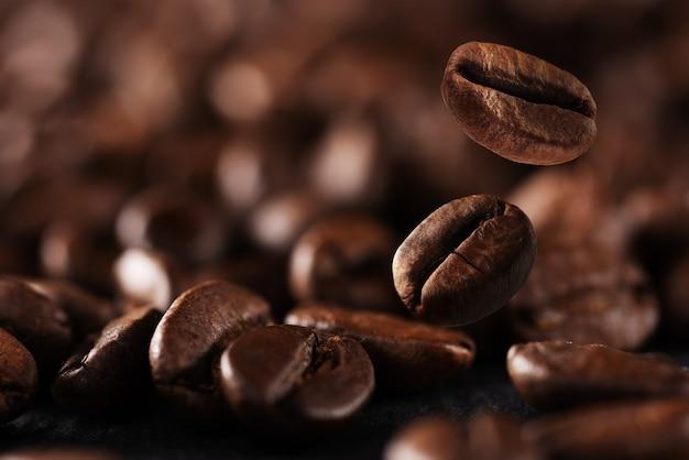 Fallender gerösteter kaffeebohnenhintergrund mit kopienraum. kaffeebohnen in der fabrik. kaffeebohnen fallen auf den tisch.