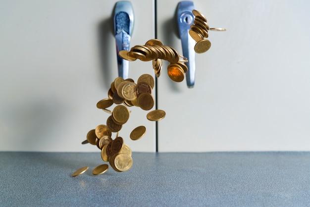 Fallendes goldmünzegeld auf bürotisch mit dokumentenschrankhintergrund