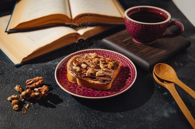Fallendes kakaopulver auf eine scheibe brot mit schokoladenaufstrich und alten vergilbten büchern