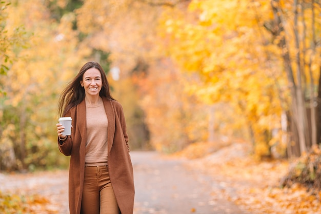 Fallkonzept - trinkender kaffee der schönheit im herbstpark unter herbstlaub