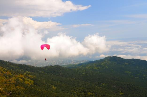Fallschirmspringer fliegen über die berge und felsen. weiße wolken am himmel