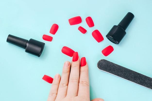 Falsche fingernägel, nagelfeile und gel-nagellack. flach lag auf einem türkisfarbenen tisch