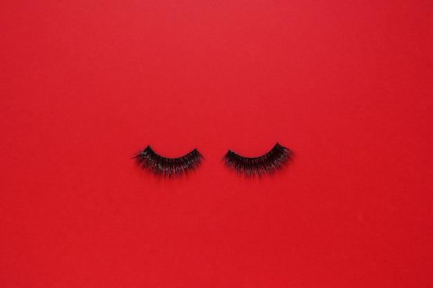 Falsche wimpern auf rotem hintergrund mit copyspace. beauty-konzept
