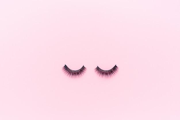 Falsche wimpern, die auf rosa liegen.