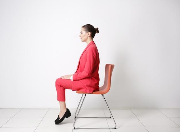 Falsches haltungskonzept. junge frau, die auf stuhl gegen weißen wandhintergrund sitzt