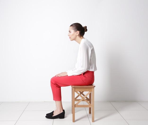 Falsches haltungskonzept. junge frau sitzt auf hocker vor weißem wandhintergrund