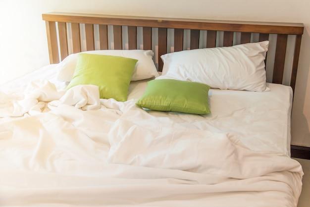 Falten sie unordentliche weiße decke im schlafzimmer, nachdem sie morgens aufwachen