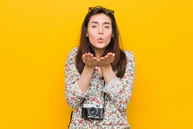 Faltende lippen der jungen brunettereisendfrau und halten von palmen, um luftkuss zu senden.