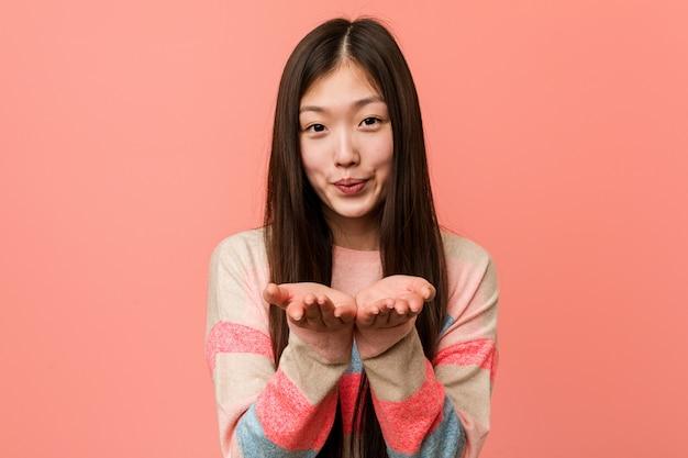 Faltende lippen der jungen kühlen chinesischen frau und holdingpalmen, zum des luftkusses zu senden.