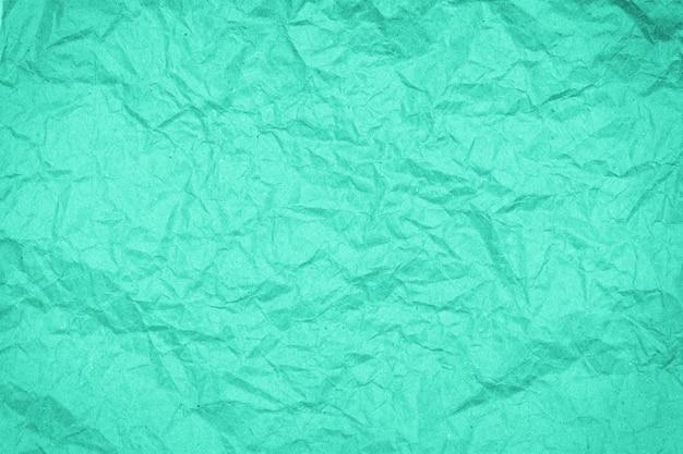 Faltige papierbeschaffenheit des abstrakten verpackungshandwerks, hintergrund, getönt in biskaya-grün