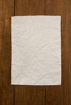 Faltiges briefpapier auf hölzernem hintergrund