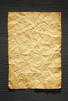 Faltiges papier am hölzernen hintergrund