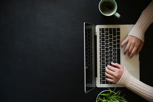 Famale, der mit laptop auf dem dunklen ledernen bürodesktop und kopienraum arbeitet