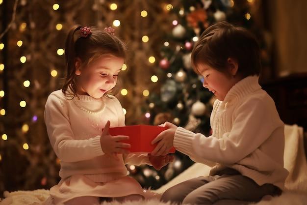 Familie am heiligabend am kamin. kinder öffnen weihnachtsgeschenke. kinder unter weihnachtsbaum mit geschenkboxen. dekoriertes wohnzimmer mit traditionellem kamin. gemütlicher warmer winterabend zu hause.