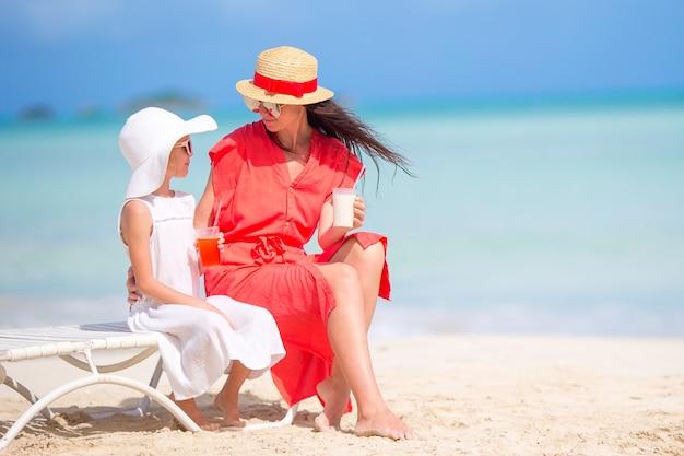 Familie am strand sitzen auf den liegestühlen