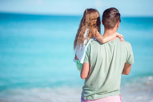 Familie am tropischen strand zusammen gehend