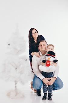 Familie am weihnachtsbaum. frau und kind isoliert auf einem weißen.