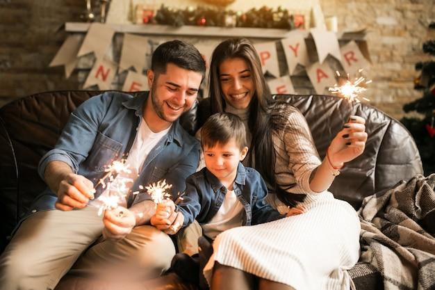 Familie an weihnachten mit bengalischen lichtern
