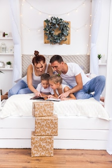 Familie auf dem bett liegend. winterurlaub weihnachten und neujahr konzept