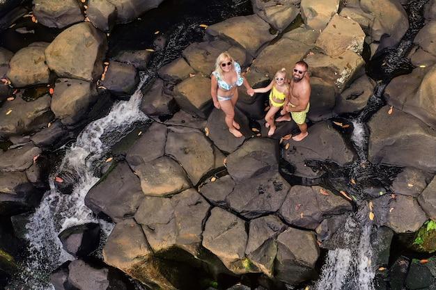 Familie auf dem hintergrund des rochester-wasserfalls auf der insel mauritius aus der höhe. wasserfall im dschungel der tropischen insel mauritius
