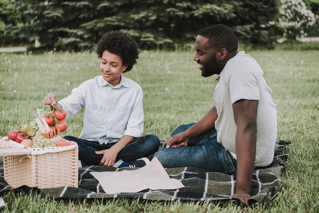 Familie auf dem picknick und jungen, die tomaten halten