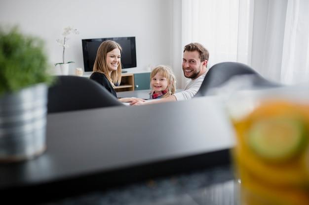 Familie auf dem sofa, das kamera betrachtet
