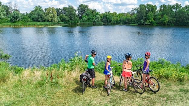 Familie auf den fahrrädern, die draußen, aktive eltern und kinder auf fahrrädern, luftdraufsicht der glücklichen familie mit den kindern sich entspannen nahe schönem fluss von oben, sport und eignungskonzept radfahren