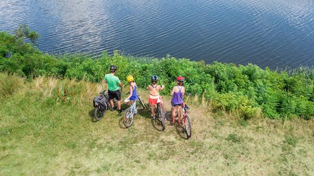 Familie auf den fahrrädern, die draußen auf fahrräder radfahren