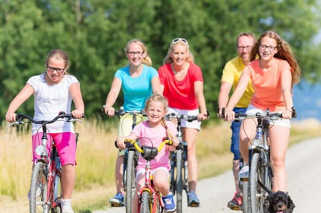 Familie auf fahrrädern am feldweg