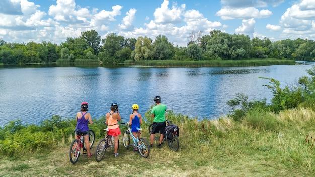 Familie auf fahrrädern, die draußen radfahren