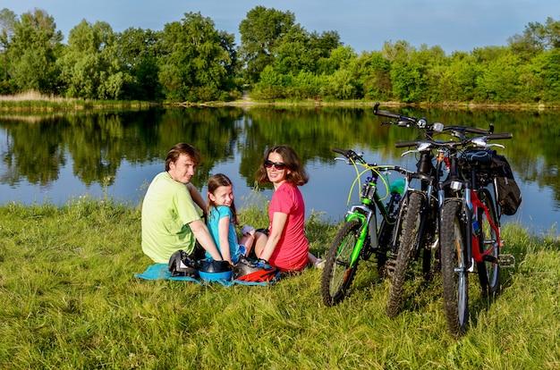 Familie auf fahrrädern draußen, aktive eltern und kind, die nahe schönem fluss, eignungskonzept radfährt und sich entspannt
