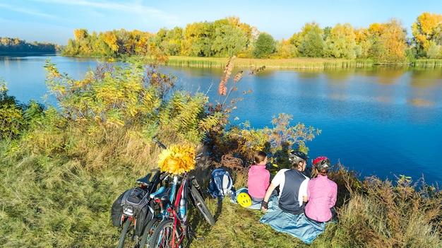 Familie auf fahrrädern herbstradfahren im freien, aktive eltern und kind auf fahrrädern, luftaufnahme der glücklichen familie mit kind, das nahe schönem fluss von oben entspannt, sport- und fitnesskonzept