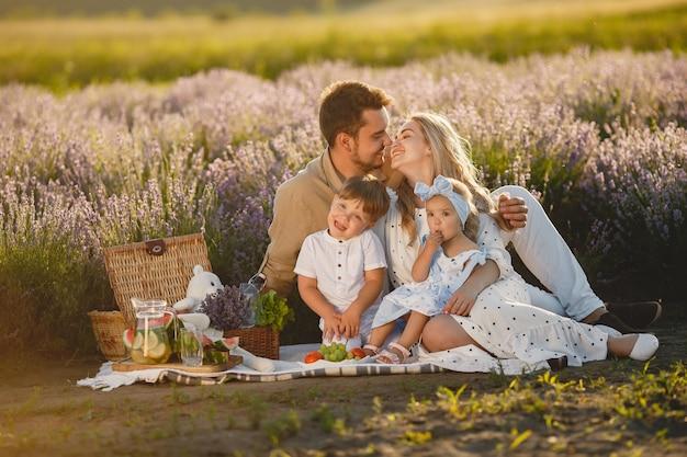 Familie auf lavendelfeld. leute auf einem picknick. mutter mit kindern isst früchte.
