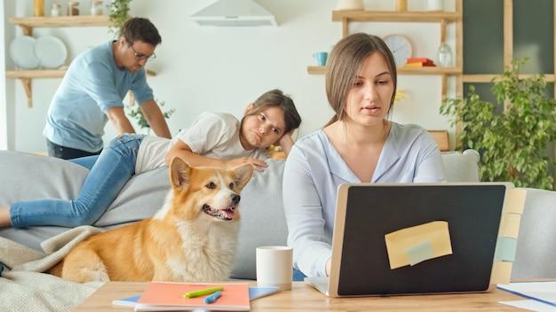 Familie auf sozialer distanzierung während der quarantäne-isolation aufgrund des coronavirus, mutter versucht aus der ferne zu arbeiten, tochter behindert die arbeit, ehemann ist in der küche beschäftigt