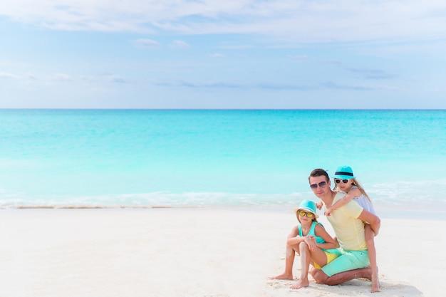 Familie auf weißem tropischem strand auf karibischer insel. vater und kleine töchter am meer