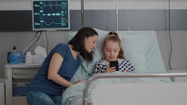 Familie begrüßt entfernten freund während einer online-videokonferenz mit einem smartphone, das in...