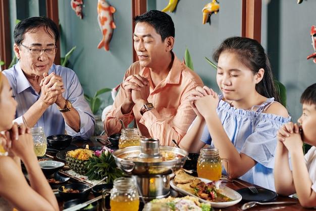 Familie betet vor dem abendessen