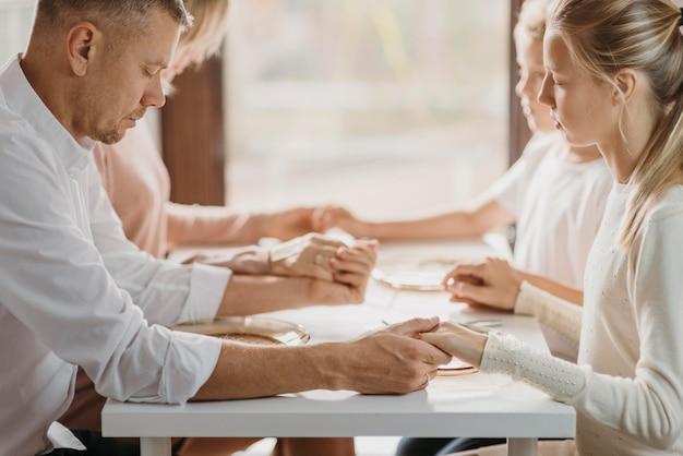 Familie betet vor dem essen